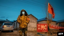 This photo taken on April 21, 2020 shows a staff member keeping watch at a checkpoint in the border city of Suifenhe, in China's northeastern Heilongjiang province. - A cluster of COVID-19 coronavirus cases in China's northeastern city of Harbin has…