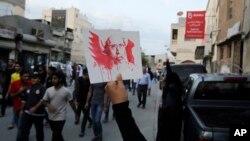Một người Bahrain giơ cao bức ảnh giáo sỹ Sheikh Nimr al-Nimr trong một cuộc tuần hành ôn hòa để phản đối vụ hành quyết ông ở Daih, Bahrain, hôm 2/2.