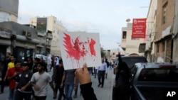 معترض ضددولتی در بحرین تصویر شیخ نمر را در دست دارد. شنبه، ۲ ژانویه ۲۰۱۶