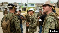 U.S. Marines and Navy corpsmen attached to the 26th Marine Expeditionary Unit and sailors assigned to Amphibious Construction Battalion 2 speak with local civilian employees during an assessment of Hospital Oriente's needs as part of Hurricane Maria relief efforts in Humacao, Puerto Rico on Sept. 27, 2017.