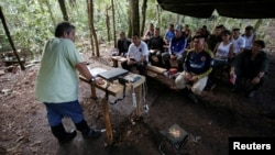 Marco Leon Calarca, (L) a member of the Revolutionary Armed Forces of Colombia (FARC), talks to members of FARC, at a camp to prepare for an upcoming congress ratifying a peace deal with the government, near El Diamante in Yari Plains, Colombia, September