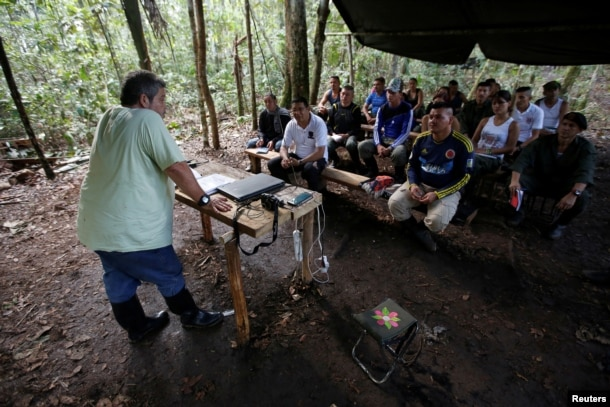 FILE - Marco Leon Calarca, (L) a member of the Revolutionary Armed Forces of Colombia (FARC), talks to members of FARC, at a camp to prepare for an upcoming congress ratifying a peace deal with the government, near El Diamante in Yari Plains, Colombia.
