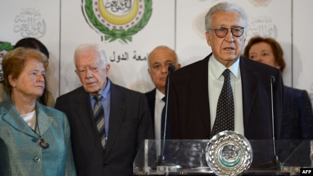 Syria peace envoy Lakhdar Brahimi, behind podium at Arab League headquaraters in Cairo Oct. 24, 2012. Seen in the background from left are former president of Ireland Mary Robinson (R) and former US president Jimmy Carter (2nd L)