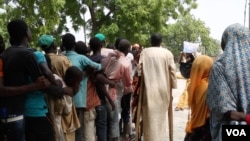 People line up along a sidewalk in front of Hajia Hawa as Yamirai Hawa passes out vouchers for free food,Maiduguri, Nigeria, Sept. 2016. (Photo: C. Oduah)