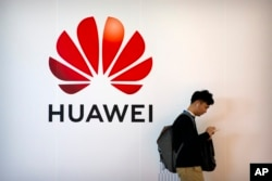 FILE - A man uses his smartphone as he stands near a billboard for Chinese technology firm Huawei at the PT Expo in Beijing, Oct. 31, 2019.