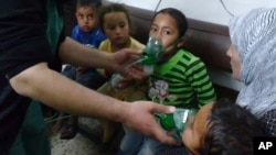 In this image taken from video obtained from the Shaam News Network, posted on April 16, 2014, an anti-Bashar Assad activist group, which has been authenticated based on its contents and other AP reporting, children are seen receiving oxygen in Kfar Zeita
