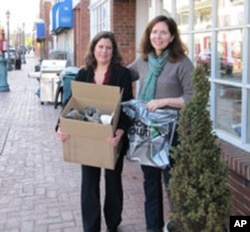 New Jersey shoe store owner Louise Van Osten and customer Jill Shobe with a carton of donated used shoes that are bound for Haiti.