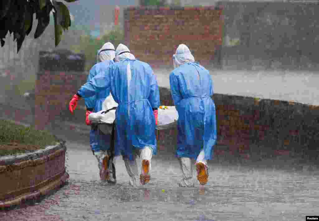 Members of Nepal Army wearing personal protective equipment (PPE) carry the body of a person, who died from the COVID-19, in the rain at the crematorium in Kathmandu.