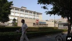 一名富士康僱員在位於廣東佛山的富士康廠房門外走過﹐這裡是富士康在中國生產蘋果產品的廠房之一。