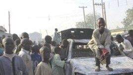 Wani yaro yake zaune kan wata motar 'Yansanda da aka kona, a wani hari da 'yan bindiga suka kai a jihar Kano.