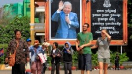 Foreign tourists, right, walk in front of Cambodia's late King Norodom Sihanouk portrait ahead of his funeral, Thursday, Jan. 31, 2013, in Phnom Penh, Cambodia. The body of Sihanouk who died on Oct. 15, 2012 at age 89, is scheduled to be cremated on Feb. 4, 2013. (AP Photo/Heng Sinith)