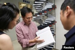 "Scientist He Jiankui shows ""The Human Genome,"" a book he edited, at his company Direct Genomics in Shenzhen, Guangdong province, China August 4, 2016."
