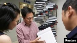 "Ilmuwan He Jiankui menunjukkan buku ""The Human Genome"", yang dia edit di perushaannya Direct Genomics di Shenzhen, Provinsi Guangdong, China, 4 Agustus 2016."
