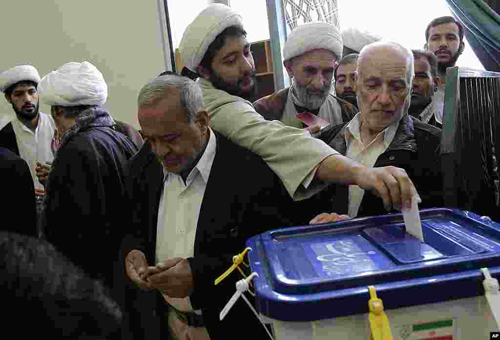 An Iranian cleric casts his ballot during the parliamentary elections at Masoumeh shrine in Qom. (AP)
