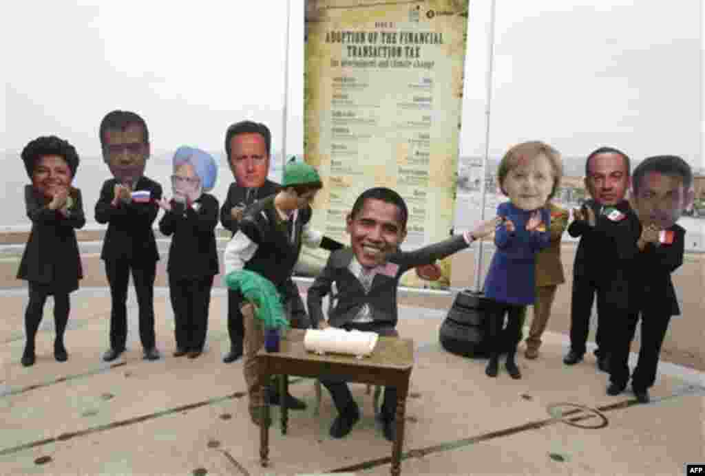 Oxam, activists wearing masks , left to right, of Brazilian President Dilma Rousseff , Russian President Dmitry Medvedev, Indian Prime Minister, Dr. Manmohan Singh, Britain's Prime Minister David Cameron, unidentified unmasked Oxfam activist, US presi