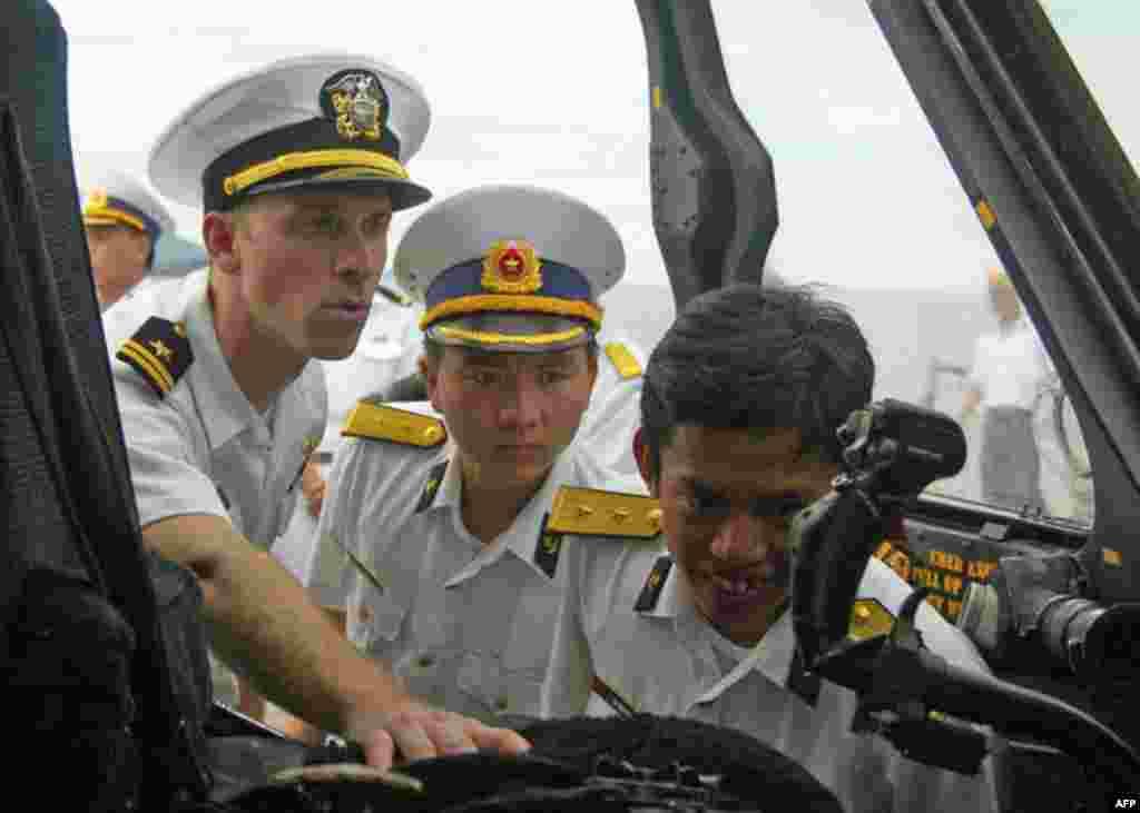 Trung úy Ross Thomas, phi công điều khiển Phi đội Trực thăng chống Tiềm thủy đỉnh 57 (HSL-57), hướng dẫn 2 đại úy hải quân Việt Nam xem buồng lái của chiếc trực thăng Seahawk SH-60B trong khi lên tham quan tàu USS Chung-Hoon (DDG 93) nhân dịp tham dự Hoạt
