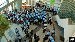 Police officers gather at the lobby of headquarters of Apple Daily in Hong Kong Thursday, June 17, 2021. (Apple Daily via AP)