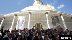 FILE - Deputies of Venezuelan coalition of opposition parties (MUD) pose for a picture in front of a giant picture of Venezuela's late President Hugo Chavez after a session of the National Assembly in Caracas, Jan. 5, 2016.