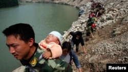 A survivor carries baby on his back as he and some 1,000 other survivors make a nine-hour walk from the village of Qingping to Hanwang, after earthquake, Sichuan Province, China, May 16, 2008.