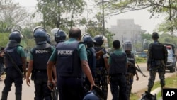 Bangladeshi policemen watch as paramilitary soldiers try to flush out Islamist radicals in the city of Sylhet, March 26, 2017.