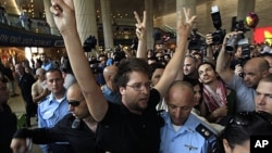 """Israeli police officers remove a pro-Palestinian Israeli activist during a small demonstration at the arrival terminal in Ben Gurion International Airport near Tel Aviv, July 8, 2011, in support of a """"fly-in"""" by other pro-Palestinian activists to Tel Aviv"""