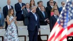 លោកប្រធានាធិបតីបារាំង Emmanuel Macron (រូបស្តាំ) និងលោកប្រធានាធិបតីអាមេរិក Donald Trump និងលោកស្រីទី១ Melania Trump មើលការដើរក្បួនយោធាក្នុងទិវា Bastille នៅលើមហាវិថី Champs Elysees ក្នុងក្រុងប៉ារីស កាលពីថ្ងៃទី១៤ ខែកក្កដា ឆ្នាំ២០១៧។
