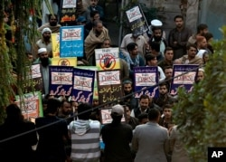 FILE - Angry protesters hold a demonstration against an independent newspaper 'Dawn' outside newspaper's office in Islamabad, Pakistan, Dec. 6, 2019.