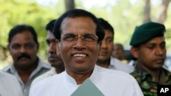 Sri Lankan Health Minister Maithripala Sirisena acknowledges the gathering as he arrives to address the media in Colombo, Sri Lanka, Friday, Nov. 21, 2014.