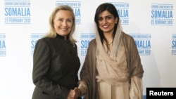 "Hillary Clinton shakes hands with Hina Rabbani Khar in London at a conference of world leaders meeting to discuss Somalia. ""Time is of the essence,"" she said. February 23, 2012 (Reuters)"