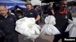馬來西亞警方負責人,在泰國邊界附近發現139個墳墓﹐圖為警方帶走屍體。