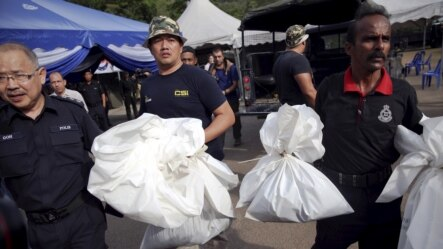 Forensic policemen carry body bags with human remains found at the site of human trafficking camps in the jungle close to the Thailand border  near Wang Kelian in northern Malaysia, May 25, 2015.