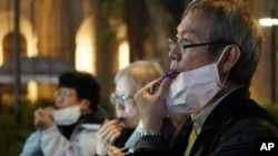 FILE - People with masks blow whistles during a vigil for Chinese doctor Li Wenliang, in Hong Kong, Feb. 7, 2020. The doctor, who was reprimanded for warning about China's new virus, died from the disease.