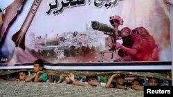 Các thiếu niên Palestine đứng dưới một tấm áp phích lớn của Hamas, để xem cuộc mít-tinh ủng hộ các phe phái vũ trang Palestine, ở Rafah, miền nam Dải Gaza, 17/8/14.