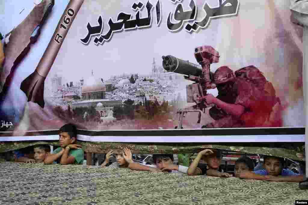 17일 가자지구 남부 라파흐의 팔레스타인 무장 지구에서 아이들이 거대한 하마스 포스터 밑으로 밖을 내다보고 있다.