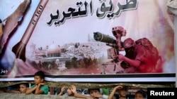 Refah kentinde dev Hamas posteri önünde silahlı militan grupların yürüyüşünü izleyen Filistinliler