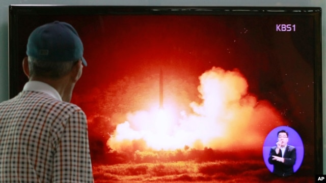 FILE - A man watches a TV news program showing a file picture of a missile launch conducted by North Korea, at Seoul Railway Station in Seoul, South Korea.