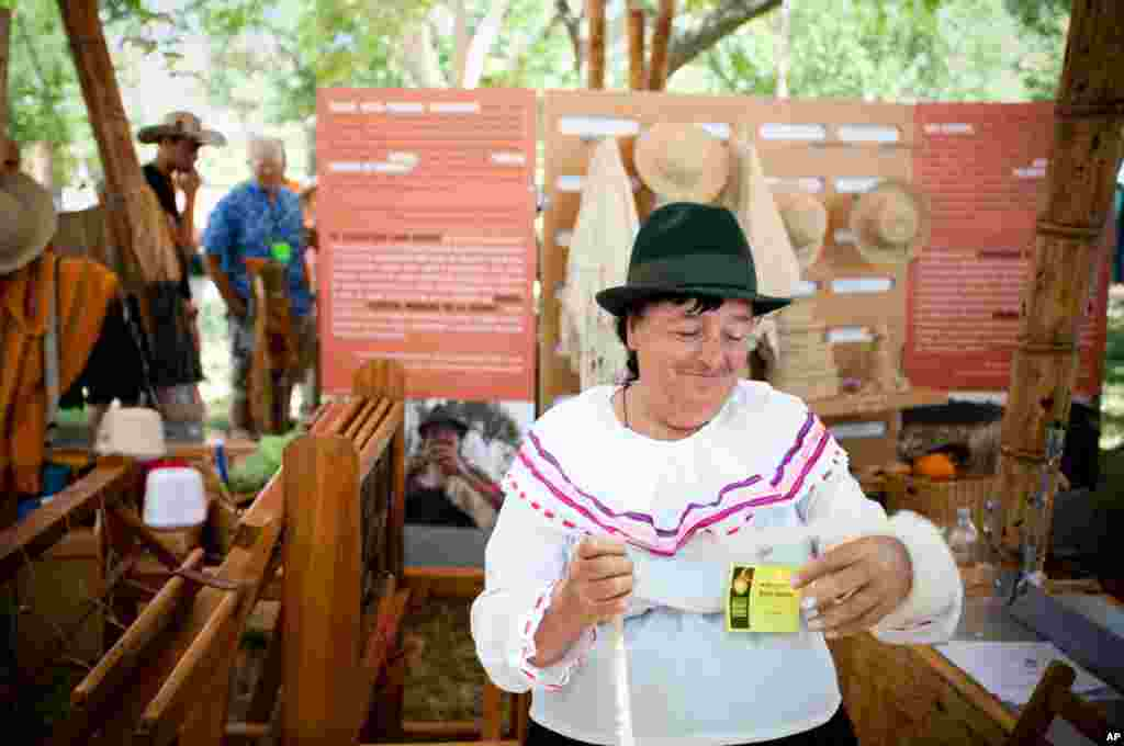 Ana Dolores Russi Suarez demonstrates the wool-weaving craft in the Colombian Village. Suarez learned this craft by watching her family and community weavers in Colombia.