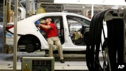Technicians work on a Toyota Corolla assembly line, Blue Springs, Mississippi, Feb. 12, 2015.
