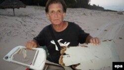 Ông Blaine Alain Gibson cầm những mảnh vỡ mới, có thể thuộc về chuyến bay mất tích MH370, vừa được tìm thấy ở đảo Nosy Boraha, Madagasca.
