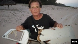 Warga Madagaskar Blaine Gibson menunjukkan potongan pesawat yang kemungkinan berasal dari pesawat Malaysia Airlines MH370 yang hilang, di pulau Nosy Boraha. (Foto: Dok)
