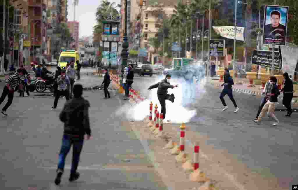 An Egyptian protester kicks a tear gas canister fired by riot police in Port Said, Egypt, March 7, 2013.