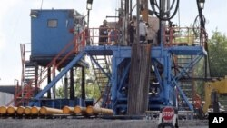 FILE - A crew works on a gas-drilling rig at a well site for shale-based natural gas in Zelienople, Pennsylvania, June 25, 2012. There has been a dramatic rise in earthquakes associated with wastewater from oil and gas drilling sites.
