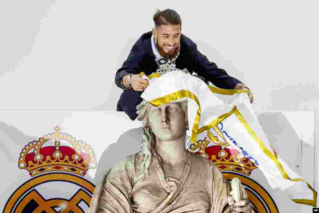 Player Sergio Ramos ties a Real Madrid flag around the neck of goddess Cibeles monument as the team arrives at Cibeles square after winning the Champions League final soccer match between Real Madrid and Atletico Madrid, in Madrid, Spain.