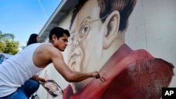 FILE - Muralist Levi Ponce paints a portrait of Mexican artist Diego Rivera in the Pacoima section of Los Angeles, June 6, 2015.