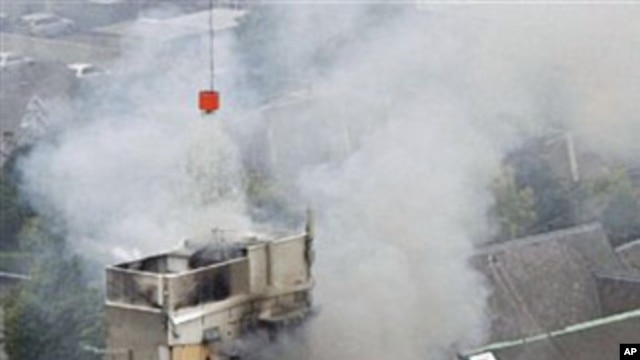 Rescue workers work to extinguish a fire at a collapsed building in central Christchurch, Feb 22 2011