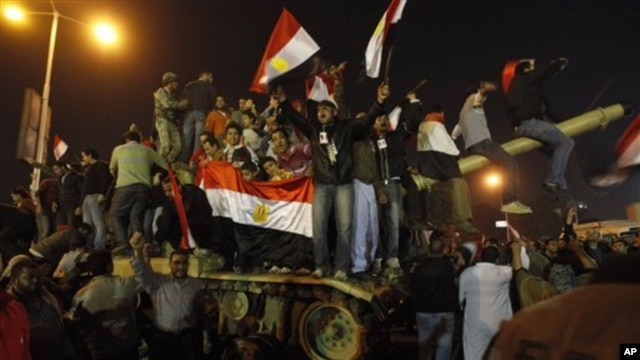 Egyptian citizens stand on an Egyptian military tank as they celebrate after President Hosni Mubarak resigned and handed power to the military at Tahrir Square in Cairo, Egypt, February 11, 2011