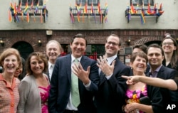 David Turley and his husband Peter Thiede display their wedding bands while posing for photos with friends and family, June 28, 2015 in front of New York's Stonewall Inn. New York Gov. Andrew Cuomo earlier wed the New York City couple.