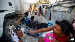 FILE - Adrienne St. Fume, at center, bags charcoal in the Delmas tent camp in Port-au-Prince, Haiti, Dec. 5, 2016. The camp aids people displaced by the 2010 earthquake. The U.S. government is reviewing Temporary Protected Status for Haitians who sought refuge in the United States after the quake.