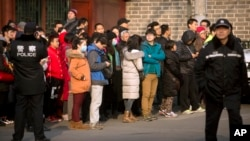 FILE - Chinese police watch as depositors from Ezubao gather in Beijing, Jan. 1, 2016. Chinese state media reported police arrested 21 employees at China's largest online finance business, Jan. 31, 2016.