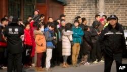 Polisi China mengawasi investor dari Ezubao berkumpul di Beijing, 1 Januari 2016. Media pemerintah China melaporkan polisi telah menangkap 21 pegawai bisnis keuangan online China terbesar itu pada 31 Januari 2016.